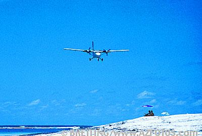 Travel picture with air plane landing at island with travellers. Stock photo from A-Z Fotos.